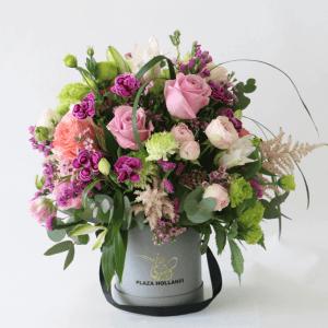 european design of purple roses, ranunculus, astilbe, carnations arranged in a plaza hollandi box