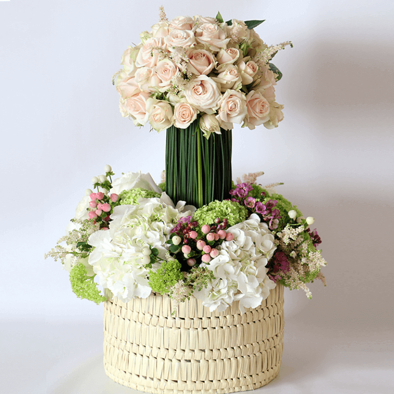 Spray rose, astilbe on a steal grass podium on white hydrangea, hypericum and snowball in a basket