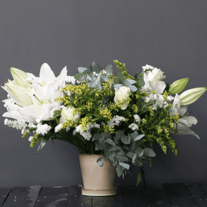 white lily and spray rose with solidago in a ceramic pot