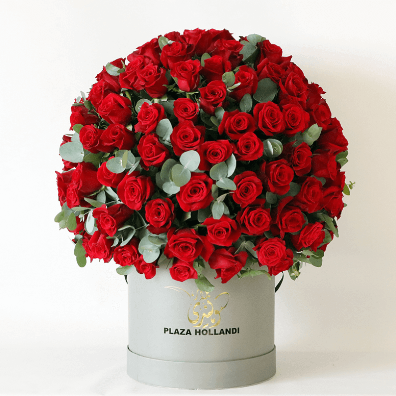 red roses arranged in a round design with eucalyptus in a Plaza Hollanndi hat box