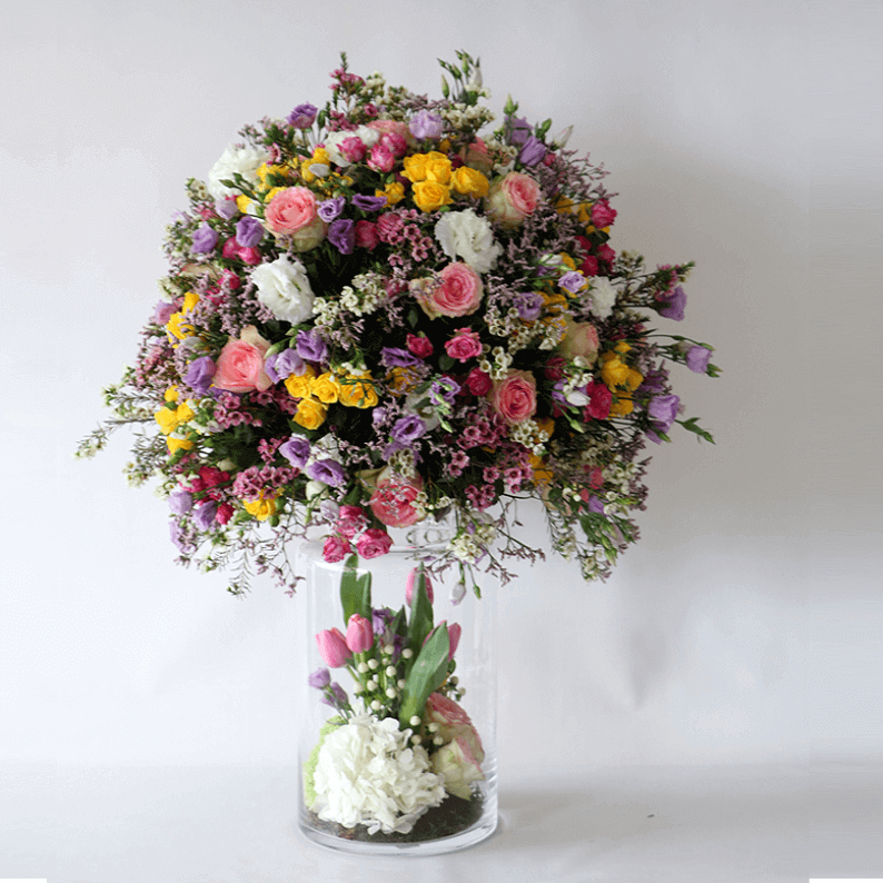 mixture of spring flowers in a tall vase