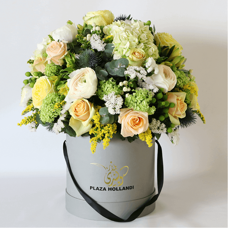 yellow and green flowers arranged in a dome in a plaza hollandi box