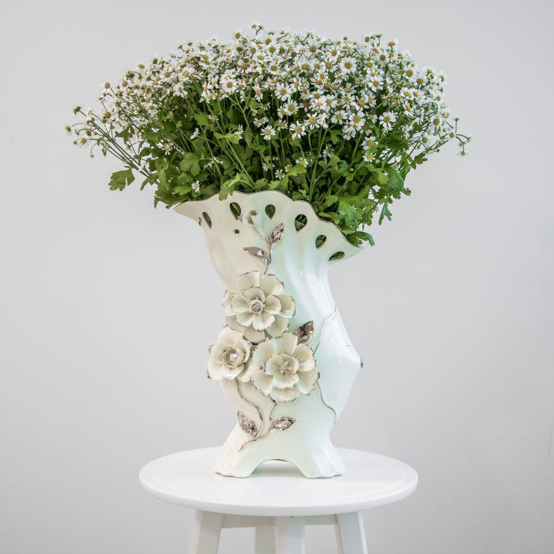Cream vase with chamomile flowers