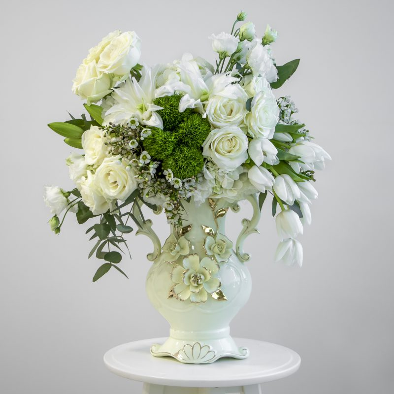 White vase filled with roses, tulips and lily