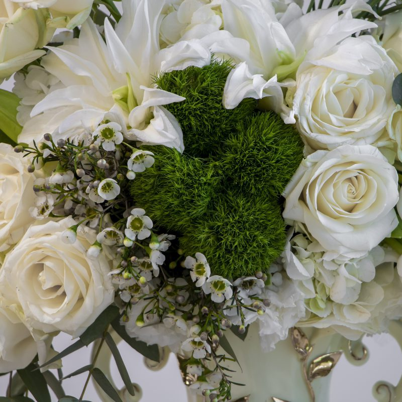 Close up of lilies, roses, and wax flower