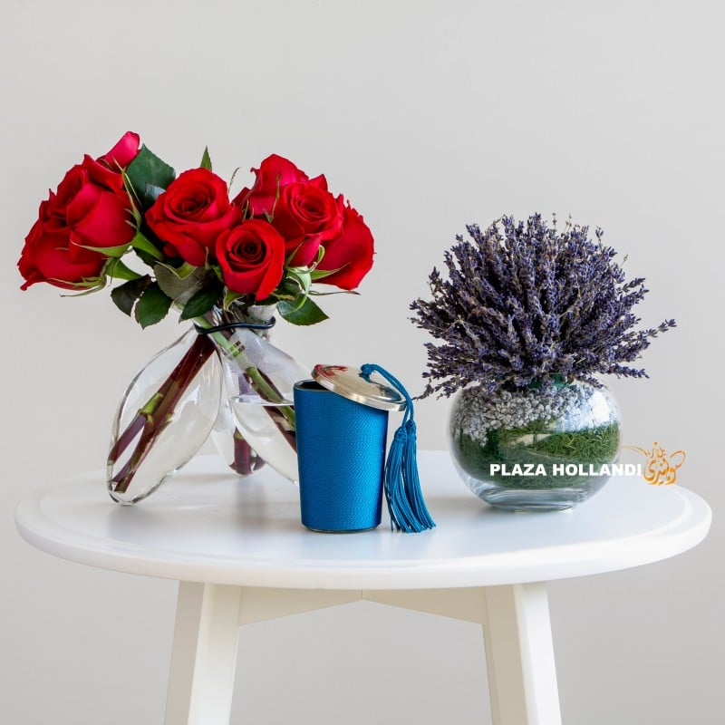 Red roses, lavender in a glass vase with a candle
