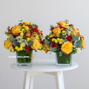 two glass vases full of yellow and red flowers
