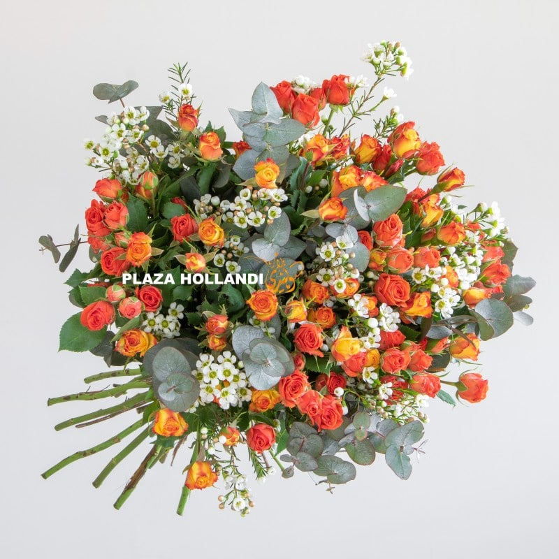Close up of wax flower and orange spray rose bouquet